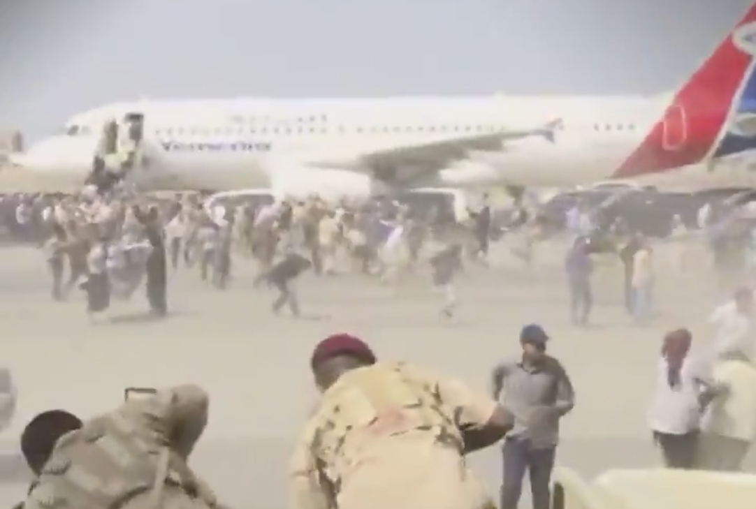 Crowds scurrying moments after the first explosion at Aden airport