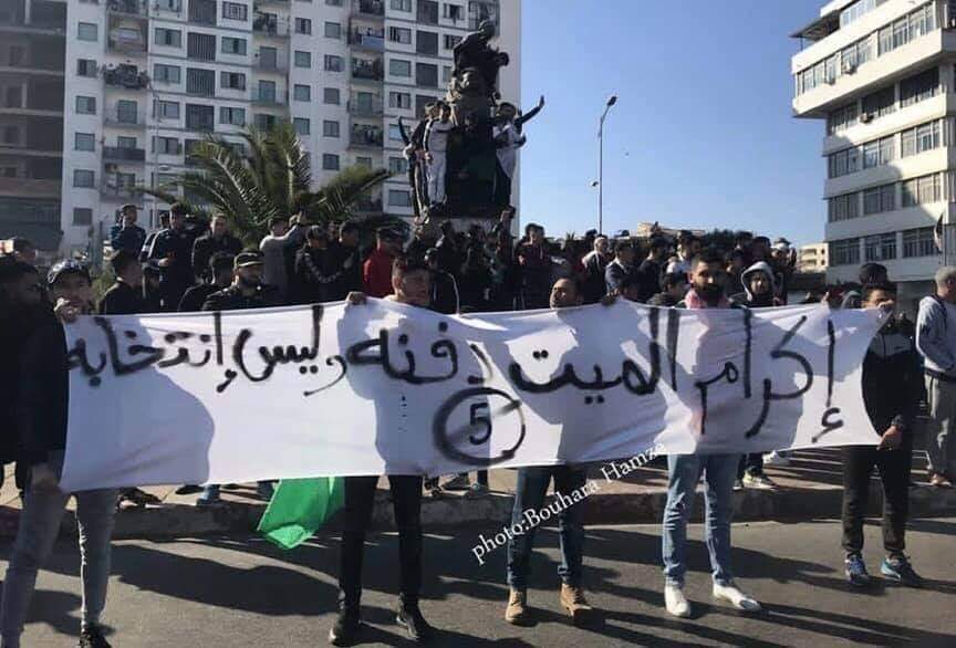 "Street protest in Algeria. The banner, referring to President Bouteflika's poor health, says: ""Respect the dead man by burying him, not electing him."""