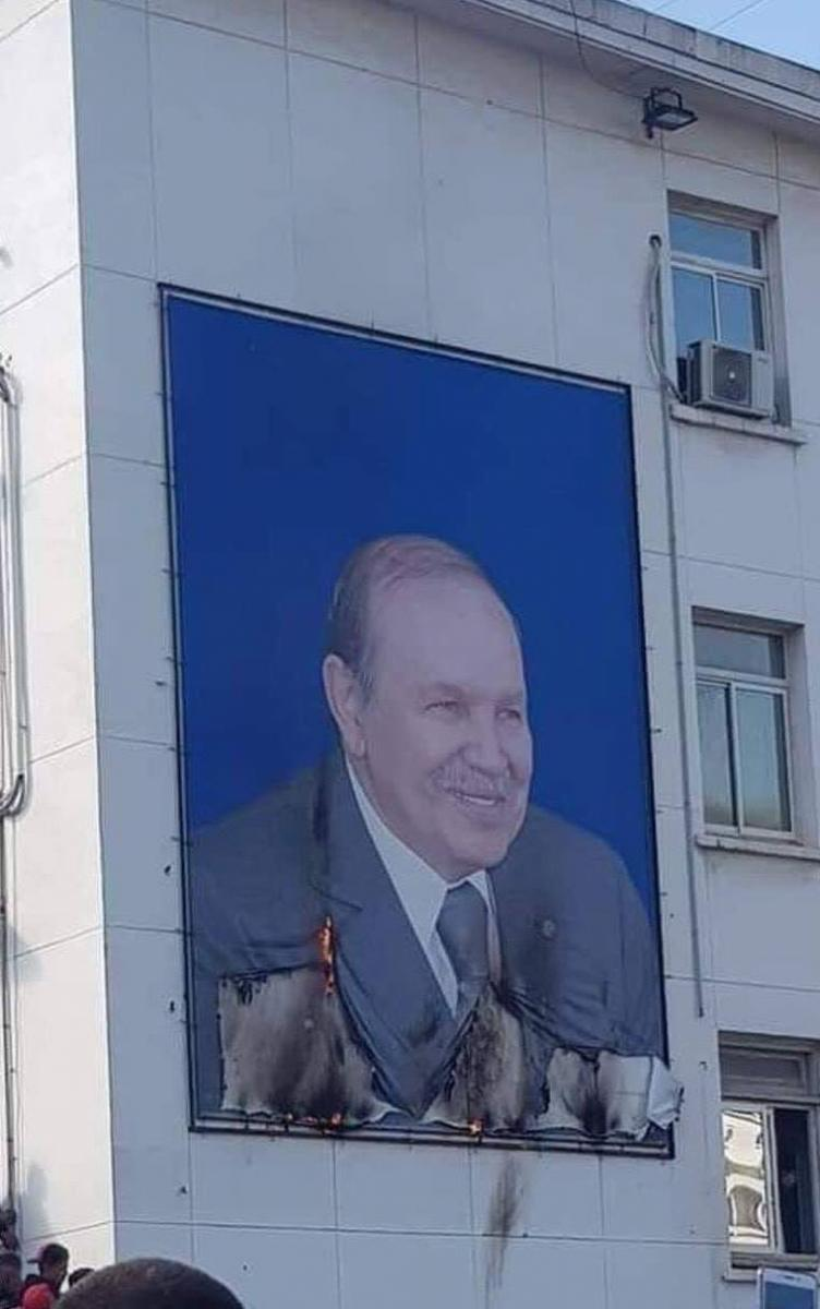 A poster of Bouteflika, partially burned by protesters
