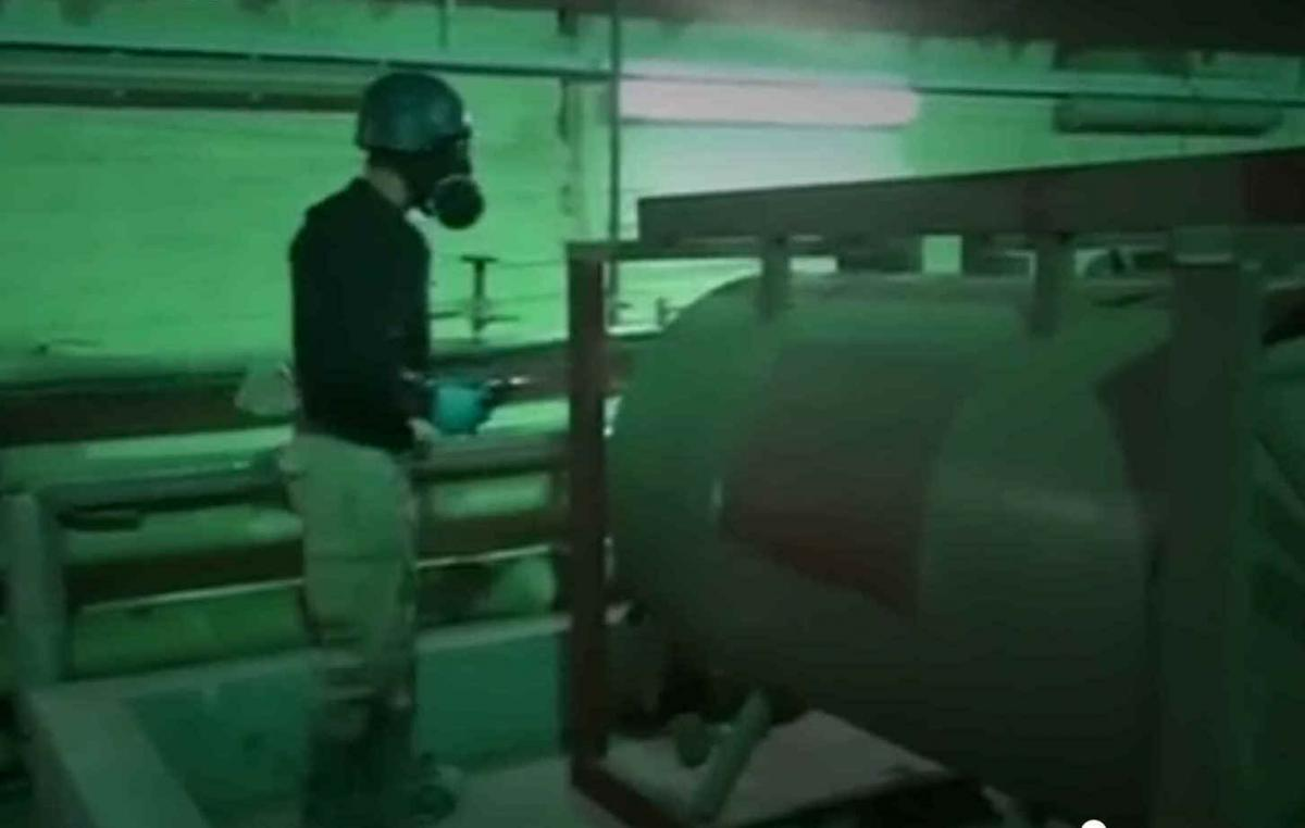 An inspector from OPCW examines tanks used in Syria's chemical weapons programme